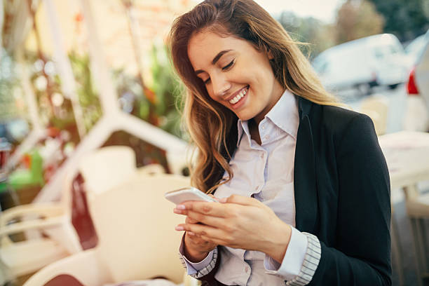 happy businesswoman using phone - text messaging stock photos and pictures
