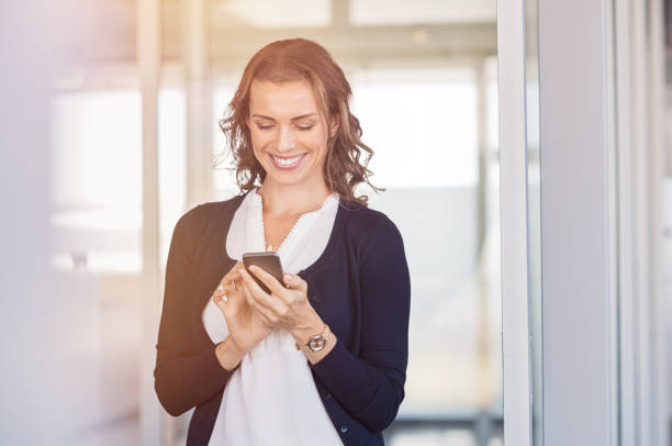 Happy businesswoman using phone stock photo