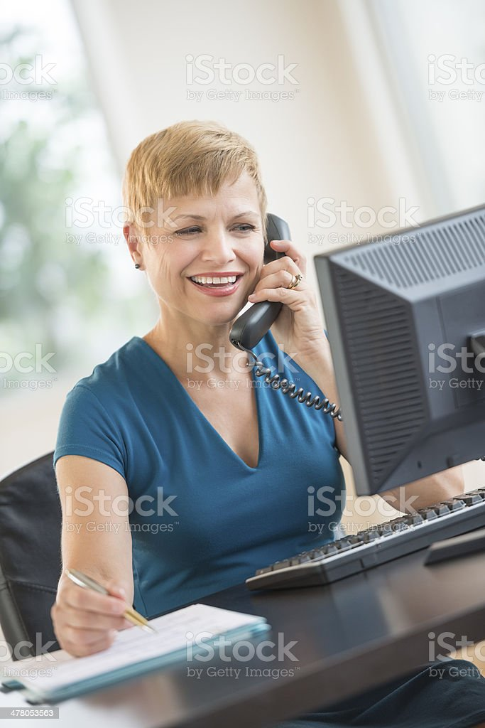 Happy Businesswoman Using Telephone At Desk royalty-free stock photo