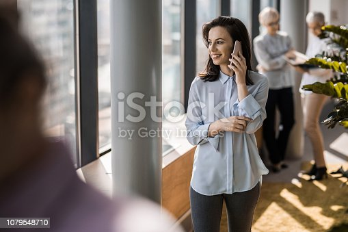 Young businesswoman talking on mobile phone while walking in a hallway of an office building.