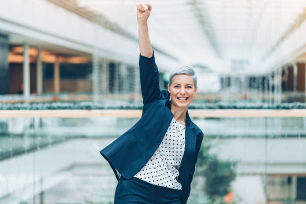 Cтоковое фото Happy businesswoman with arm raised in triumph