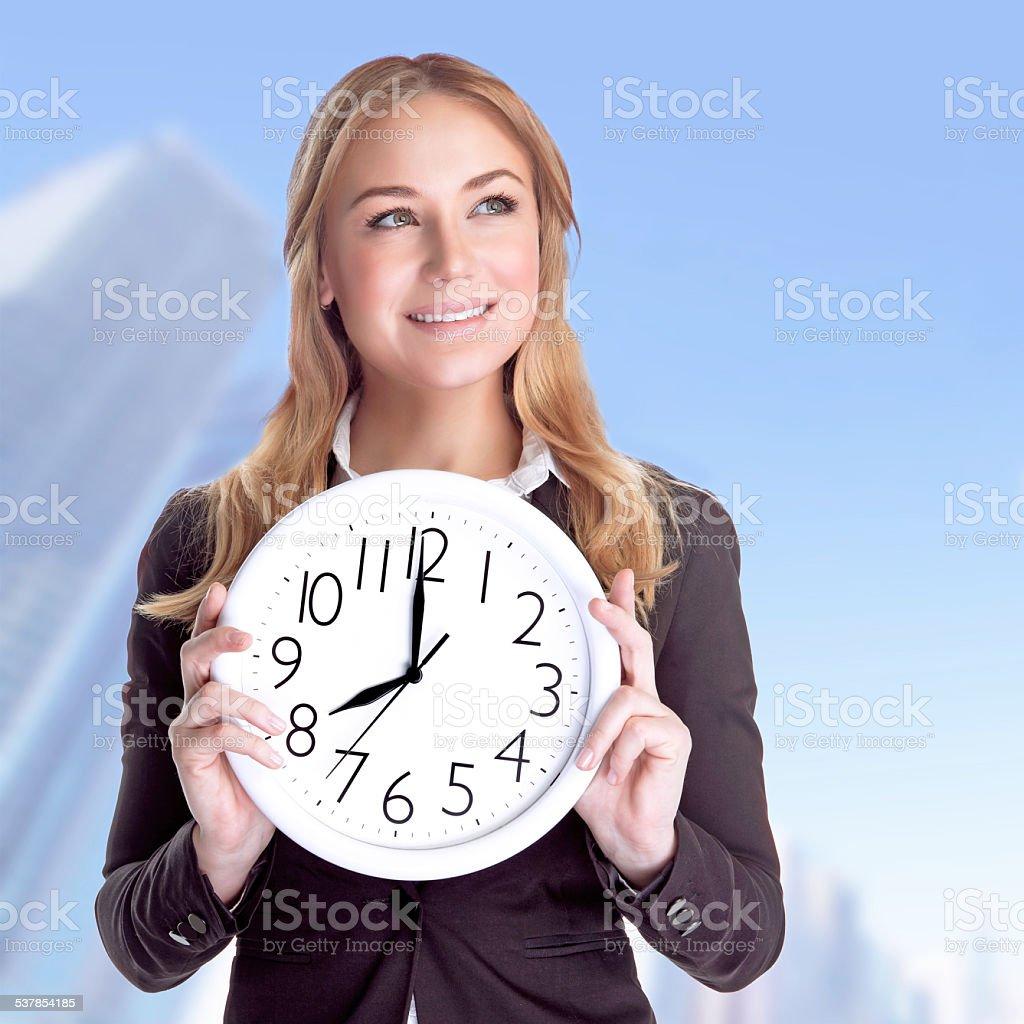 Happy businesswoman with big clock stock photo