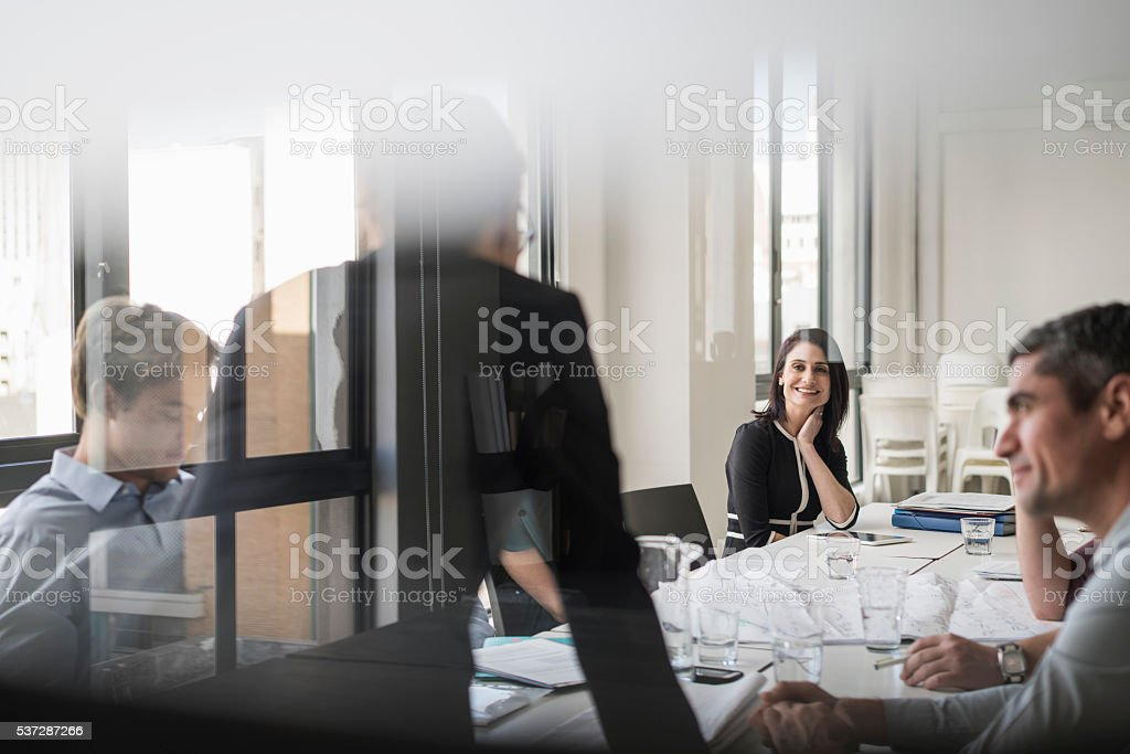 Happy businesswoman with colleagues in board room stock photo