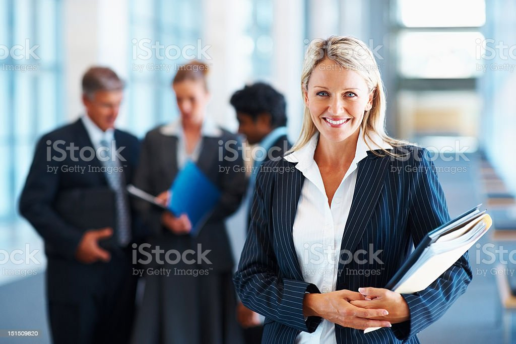Happy businesswoman with colleagues in the background Happy businesswoman with colleagues in the background 40-44 Years Stock Photo