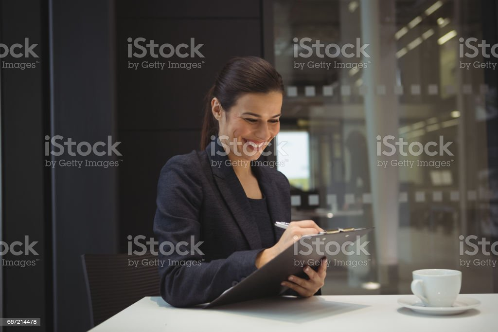 Happy businesswoman writing on clipboard royalty-free stock photo