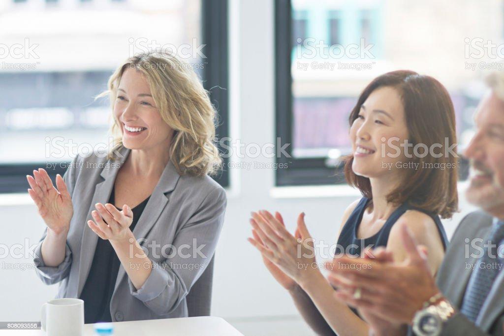 Happy businesswomen applauding in board room stock photo
