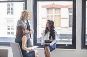 Happy businesswomen discussing by window in office