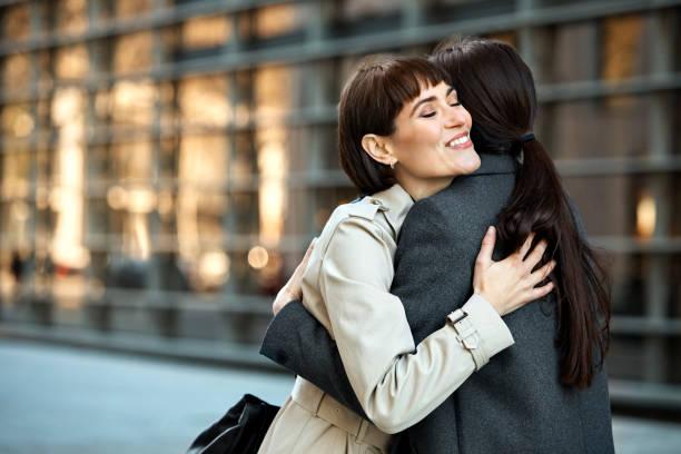 glücklich geschäftsfrauen umarmen einander in stadt - winterjacke lang damen stock-fotos und bilder