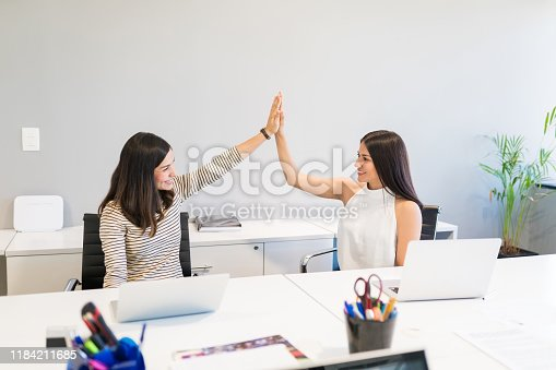 1031394114 istock photo Happy Businesswomen Giving High-Five After Success At Desk 1184211685