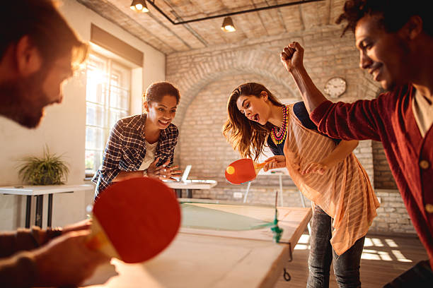 happy businesswomen playing table tennis against businessmen at casual office. - table tennis stock pictures, royalty-free photos & images