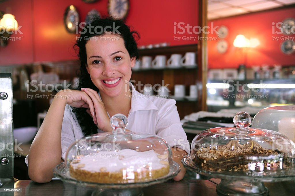 A happy cafe owner posing behind a cake royalty-free stock photo