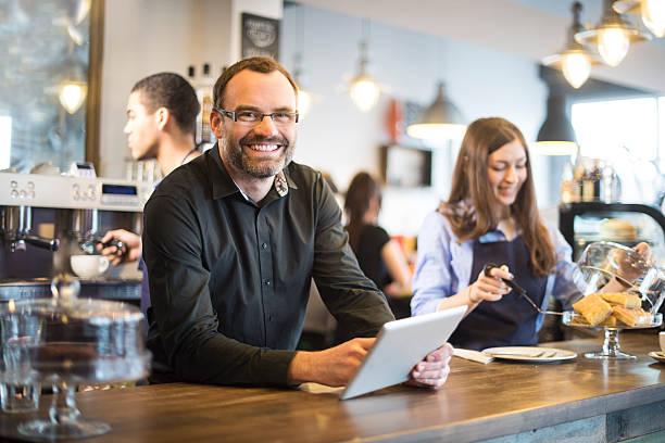 glücklich café-besitzer aktualisierung social media mit einem digitalen tablet - brille bestellen stock-fotos und bilder