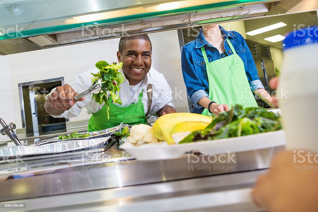 Happy cafeteria worker serving salad to student in lunch line stock photo