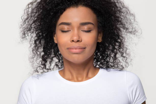 Happy calm african woman taking deep breath of fresh air Happy calm african woman with beautiful face take deep breath of fresh air, grateful mindful black lady enjoy inhaling meditating feel no stress free harmony isolated on white grey studio background relief emotion stock pictures, royalty-free photos & images