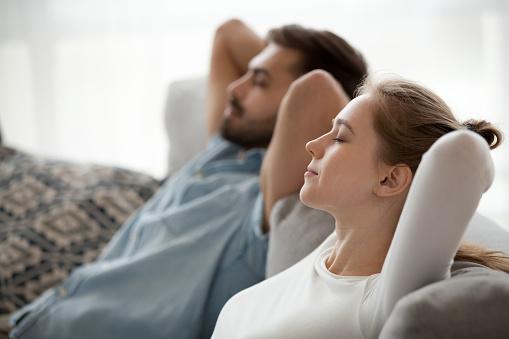973962076 istock photo Happy calm couple enjoying relaxation having nap on sofa breathing 1124667802