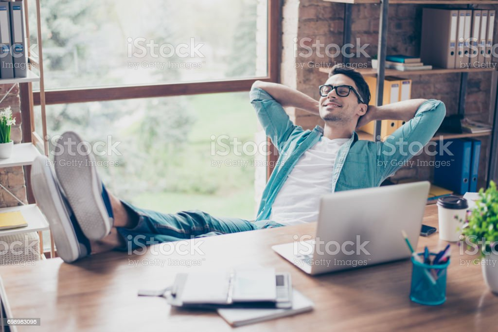 Happy calm smiling man having a rest after solving all the tasks at work stock photo