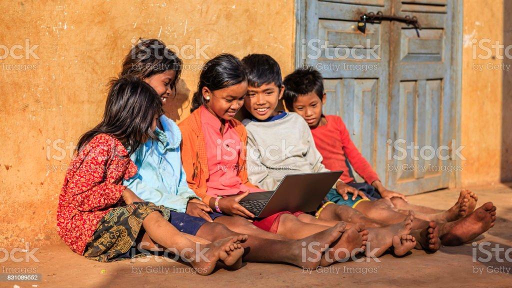 Happy Cambodian children using laptop on a schoolyard, Cambodia stock photo