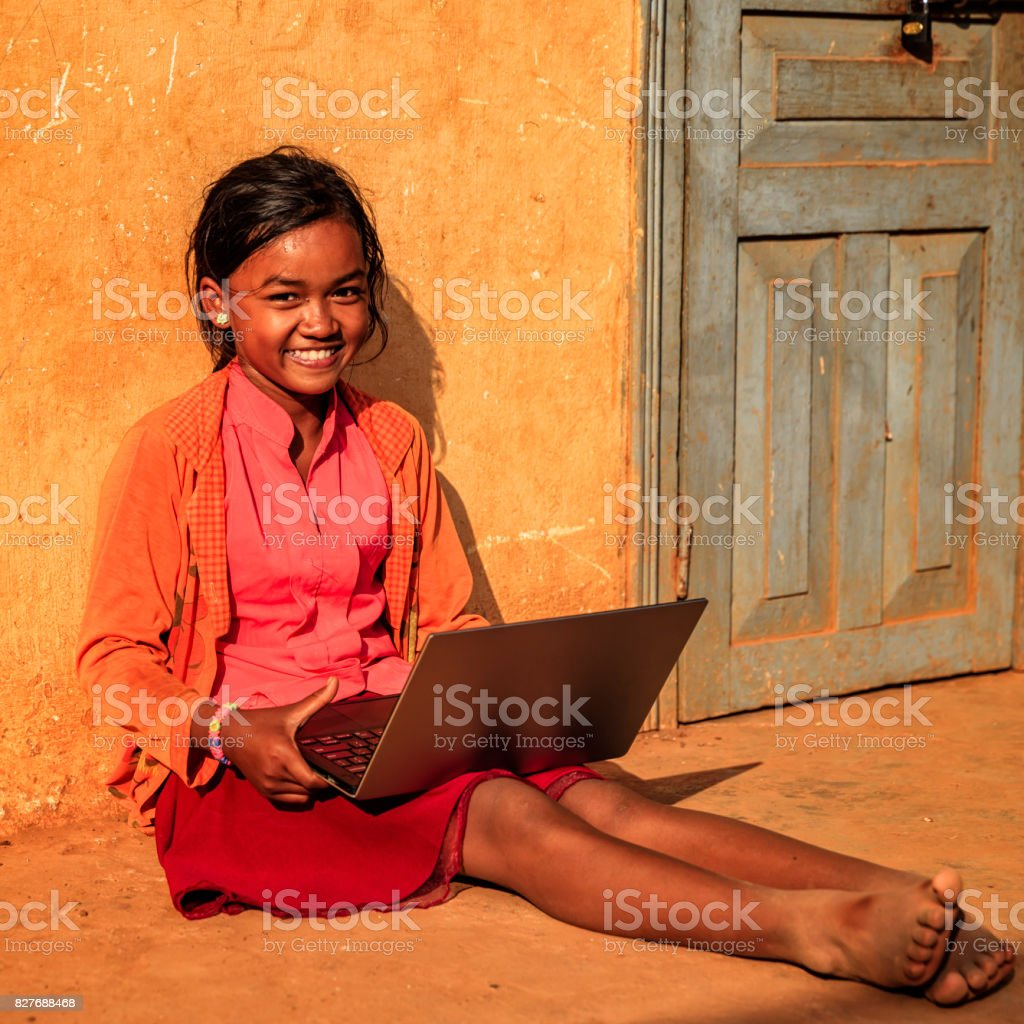 Happy Cambodian little girl using laptop on a schoolyard, Cambodia stock photo