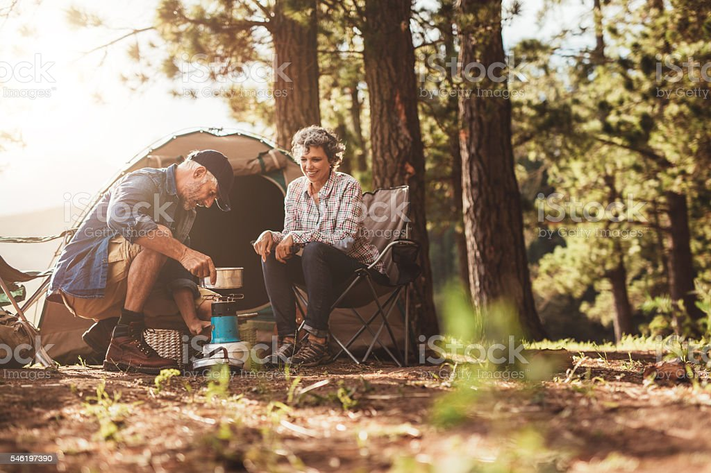 Happy campers making coffee in the wilderness stock photo