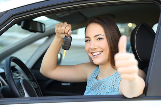 Happy car owner with a key and thumbs up stock photo
