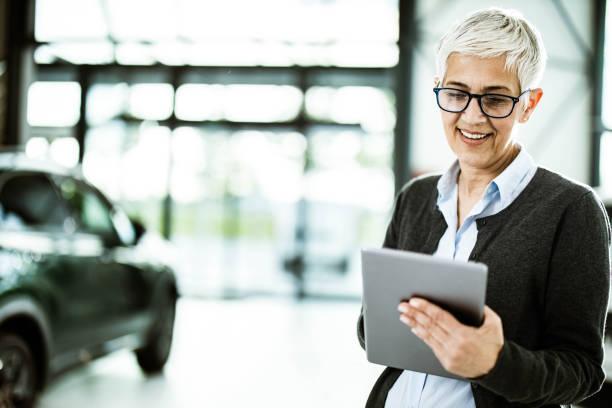 happy car salesperson using digital tablet in a showroom. - senior business woman tablet imagens e fotografias de stock