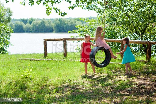happy carefree little girls baby preschooler having fun and playing on a swing wheel in the garden on a Sunny summer day. Summer outdoors activity for kids. Girls swinging on a tire