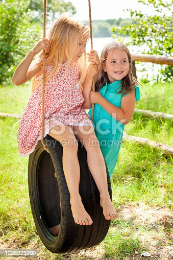 happy carefree little girls baby preschooler having fun and playing on a swing wheel in the garden on a Sunny summer day. Summer outdoors activity for kids. Child having fun and swinging on a tir