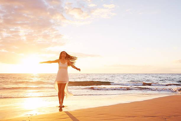 Glückliche unbeschwerte Frau Tanzen am Strand bei Sonnenuntergang – Foto