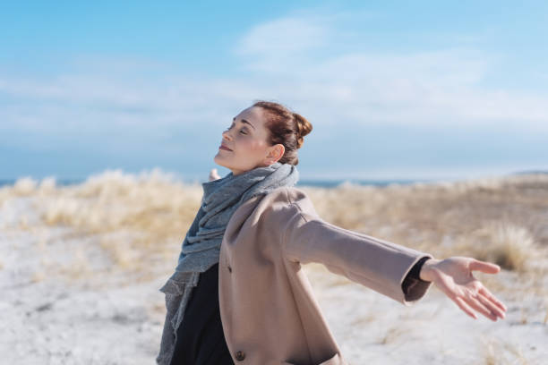 愉快的無憂無慮的年輕婦女在冬天海灘 - 僅一名中年女子 個照片及圖片檔