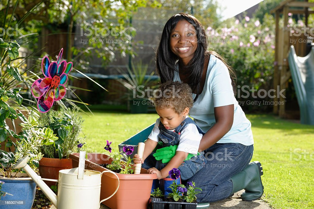 Happy Carer/ Childminder Gardening With Toddler royalty-free stock photo
