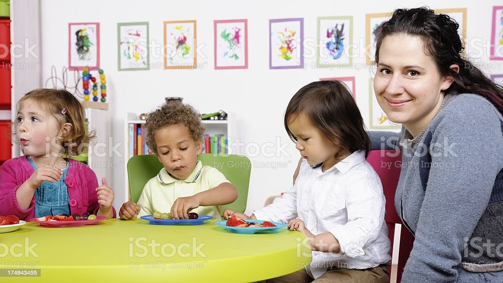 Happy Carer Supervising Group Of Little Children At Mealtime royalty-free stock photo