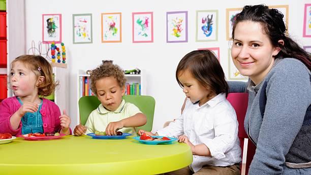 Happy Pflegekraft Beaufsichtigung der Gruppe von kleinen Kindern bei den – Foto
