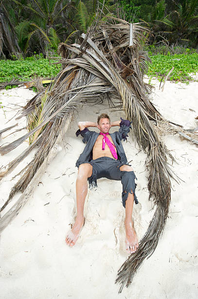 happy castaway businessman relaxes in shelter - desert island stock photos and pictures