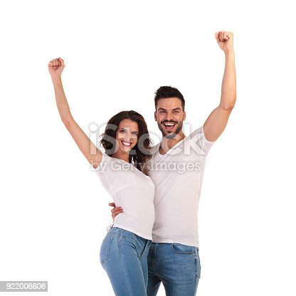 854381886 istock photo happy casual couple celebrating success with hands in the air 922006606