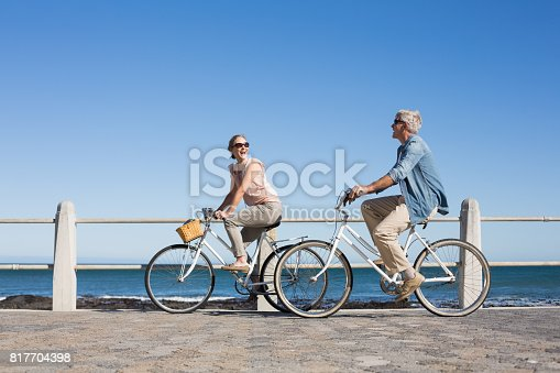 istock Happy casual couple going for a bike ride on the pier 817704398