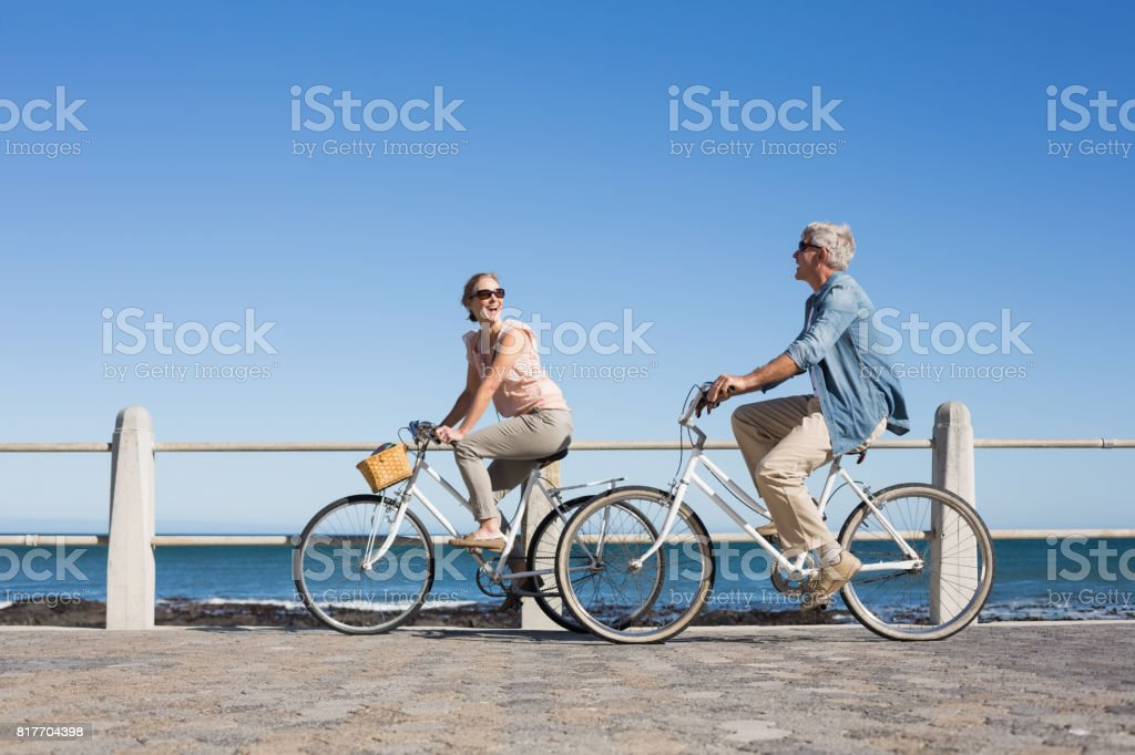 Happy casual couple going for a bike ride on the pier - fotografia de stock