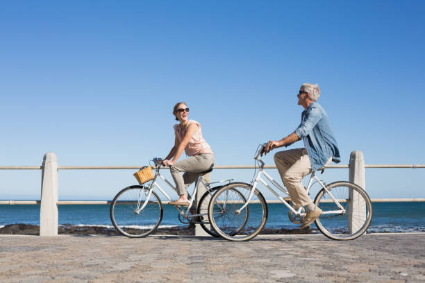 happy casual couple going for a bike ride on the pier - cycling stock photos and pictures