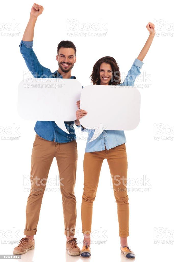 happy casual couple holding speech bubbles celebrating success stock photo