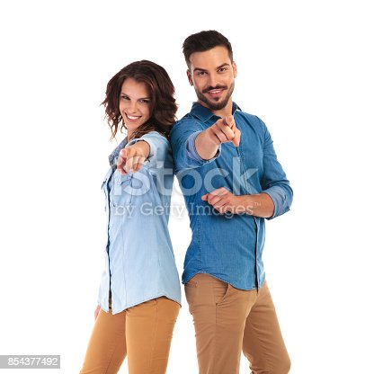 istock happy casual couple pointing fingers 854377492