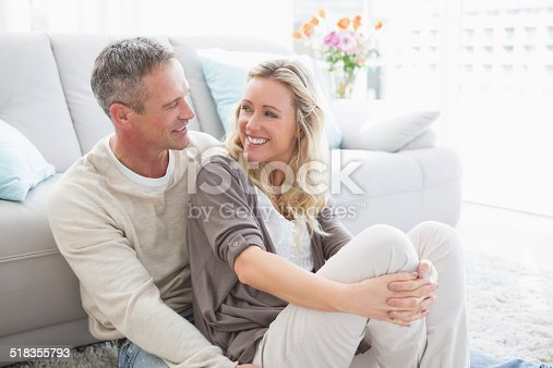 istock Happy casual couple sitting on rug 518355793