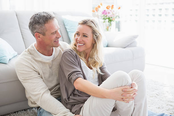 happy casual couple sitting on rug - mid volwassen stockfoto's en -beelden