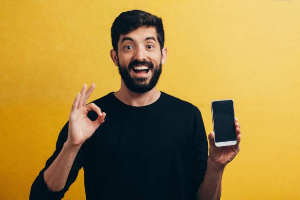 黄色の背景に空白のスマート フォンの画面と ok サインを示す幸せなカジュアルな男 - 見せる ストックフォトと画像