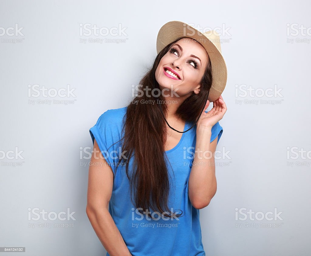 Happy casual woman in summer hat thinking about vacation stock photo