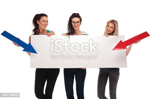 istock happy casual women pointing arrows to a big blank board 640196350