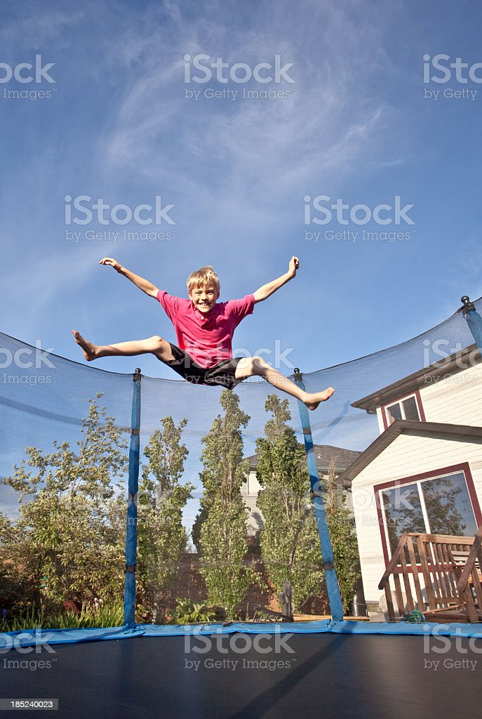 Happy Caucasian Boy Jumping on Trampoline royalty-free stock photo