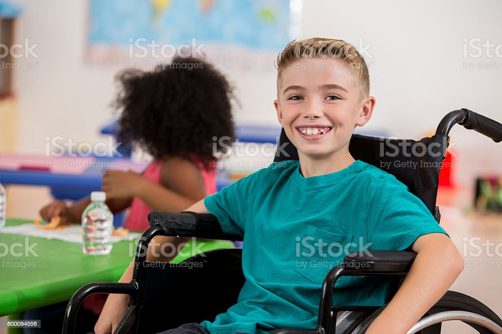 Happy Caucasian boy sitting in a wheelchair during school stock photo