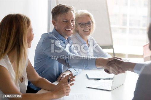 istock Happy caucasian employer hr handshake hire successful african candidate 1146468283