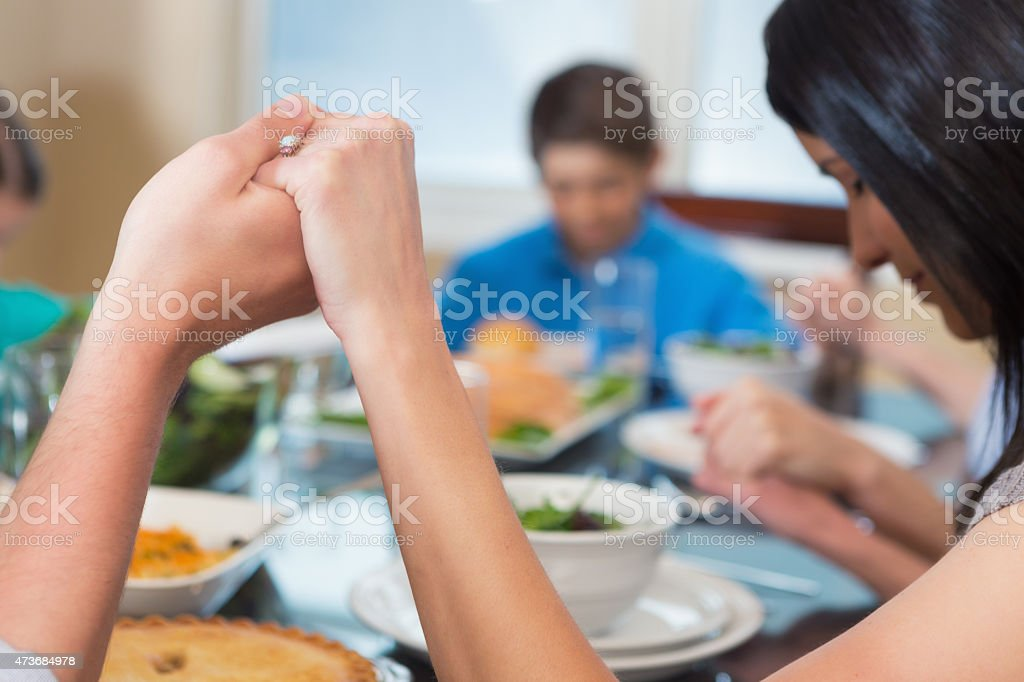 Happy Caucasian family praying around dinner table together stock photo