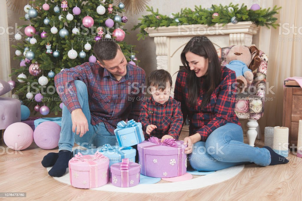 happy caucasian family sitting in christmas decorations with tree and fireplace stock photo