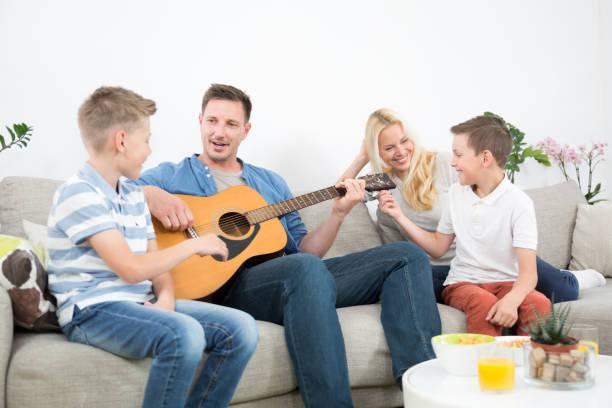 Glückliche kaukasische Familie lächelnd, Gitarre spielen und Singen Lieder zusammen in gemütlichen modernen Haus – Foto
